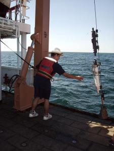 Student gets a water sampler aboard ship