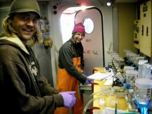 Two scientists in ship lab work on water samples
