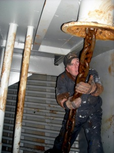 Crewman arranges anchor chain below deck