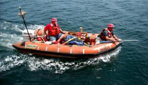 Crew members in boat during man-overboard safety drill
