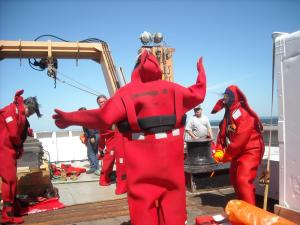 Scientists learn to get into survival suits during safety drill on deck