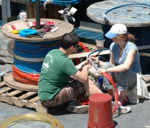 man and woman sit on deck working on hydrophone