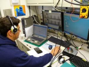 Rob with headphones on at acoyustics desk
