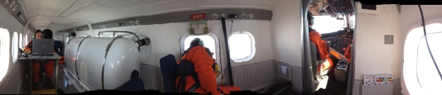 Panoramic view inside the NOAA Twin otter during a right whale survey flight.   At left, Tim Cole records data and Pete Duley is in the bubble window. Photo by Christin Hlan, NEFSc/NOAA