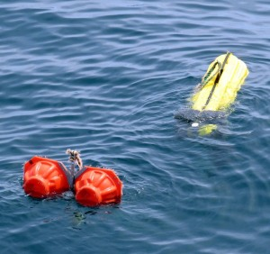 AMAR unit on the surface after being released from its mooring on the seafloor. The yellow container has part of the unit inside while the red floats are supporting another component beneath them. Photo by Jerry Prezioso NEFSC / NOAA.