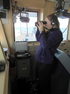 Jeannine Winkle using binoculars to sight birds from the bridge of the NOAA Ship Gordon Gunter