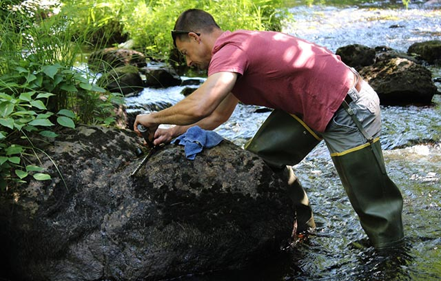 Man in waders adjusting a small instrument in the middle of a stream in Maine