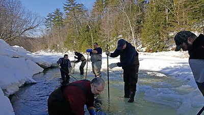 Men chipping choles in ice cover on a stream