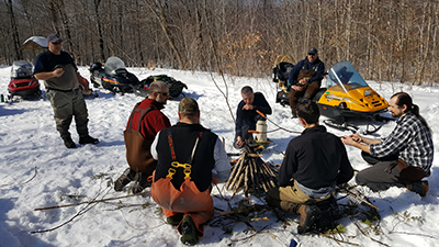 7 men around a campfire in the snow eating lunch